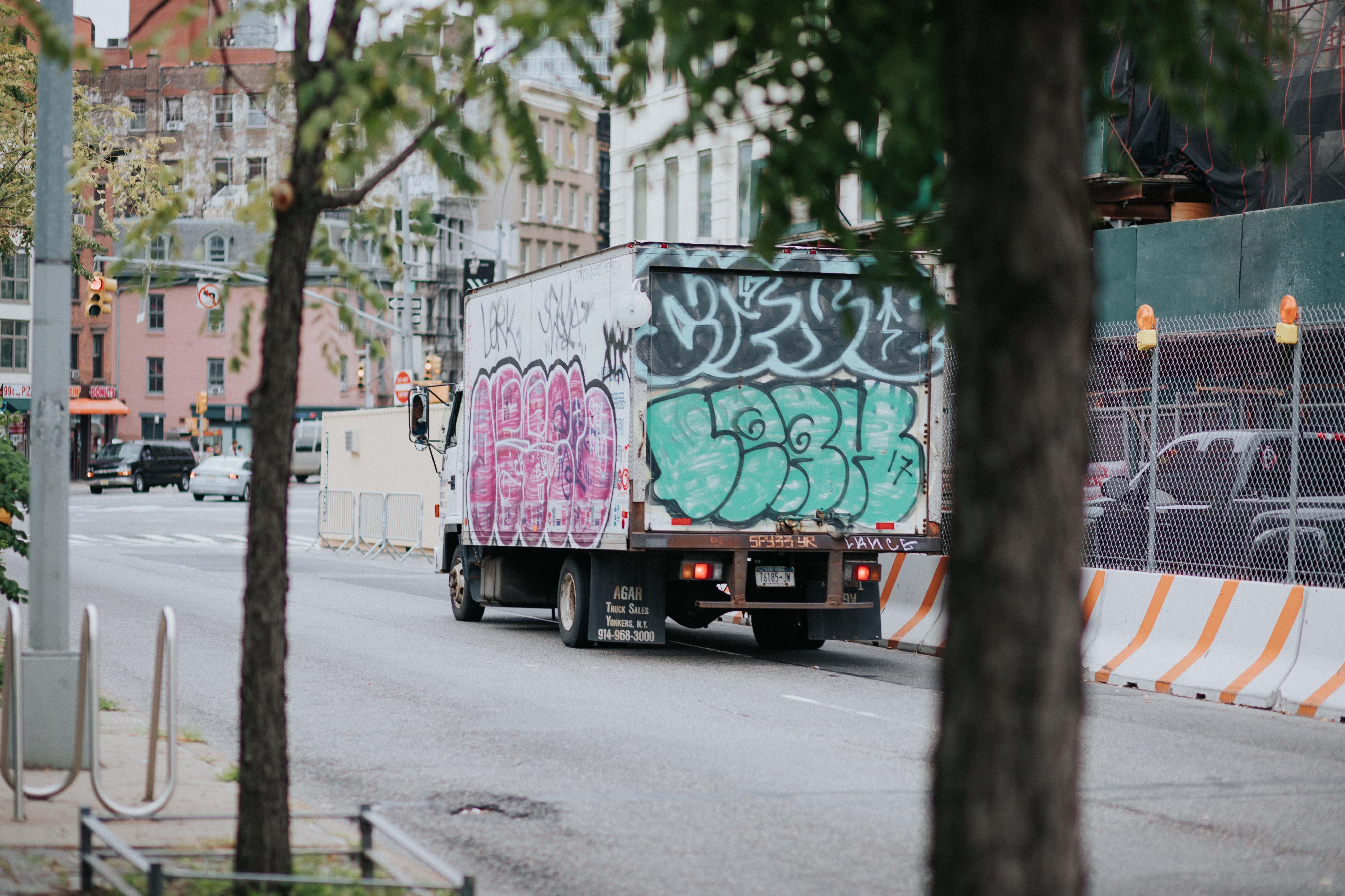 White enclosed van on road NY.